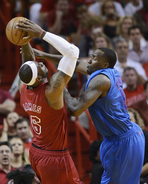 Oklahoma City Thunder's Kendrick Perkins (R) fouls Miami Heat's LeBron James (L) during the second half of their NBA basketball game in Miami, Florida, December 25, 2012.