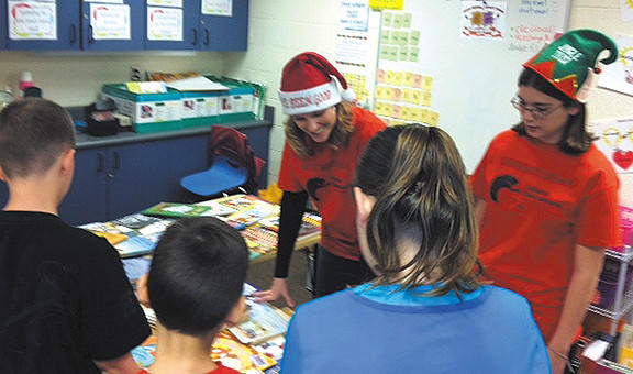 Members of Hagerstown Community College's Future Teachers of America help Salem Avenue Elementary students choose books during Salem's holiday book giveaway.
