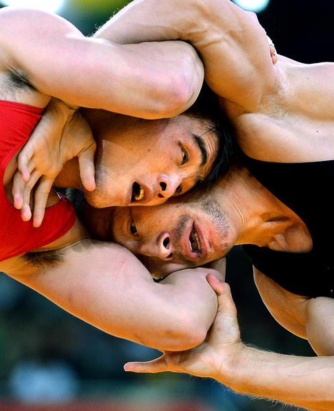 North Korea's Kyong Yang and Uzbekistan's Dilshod Mansurov battle during the quarterfinals in a wrestling match at the 2012 London Olympics.