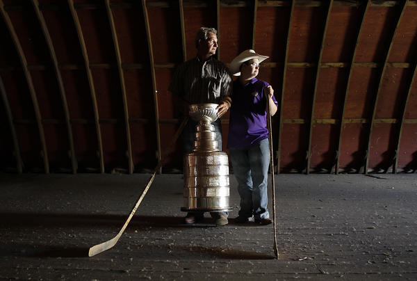 Los Angeles Kings Coach Darryl Sutter and his son, Chris, pose for a photo with the Stanley Cup at his family farm.