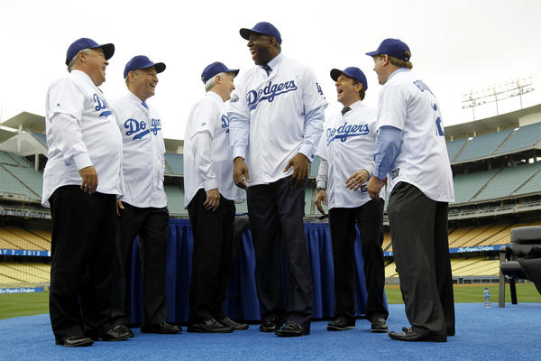 "New Dodgers owners -- the Guggenheim Baseball Management group, led by Earvin ""Magic"" Johnson, center -- pose for photos during a news conference at Dodger Stadium. Left to right are Bobby Patton, Stan Kasten, Mark Walter, Johnson, Peter Guber and Todd Boehly. They bought the team from Frank McCourt for $1.6 billion."