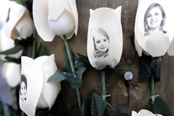 Pictures of shooting victims are imprinted on artificial roses at a memorial Saturday in the Sandy Hook neighborhood of Newtown, Conn.