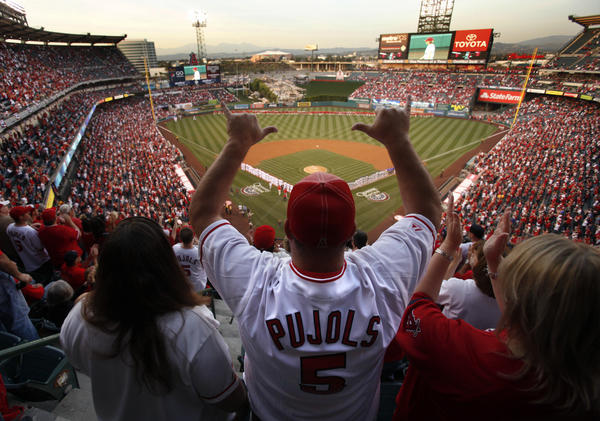 An Angels fan wearing an Albert Pujols jersey cheers during pregame festivities as the Angels get set to play the Kansas City Royals in the season opener at Angel Stadium. The Angels finished out of playoff contention despite signing Pujols, considered by many to be the best player in baseball, before the 2012 season.