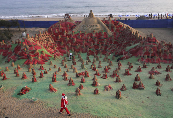 A man dressed in a Santa Claus costume walks past sand sculptures of Santa Clauses created by the artist Sudarshan Pattnaik and his students as part of Christmas celebrations on a beach in Puri, located in the eastern Indian state of Odisha.