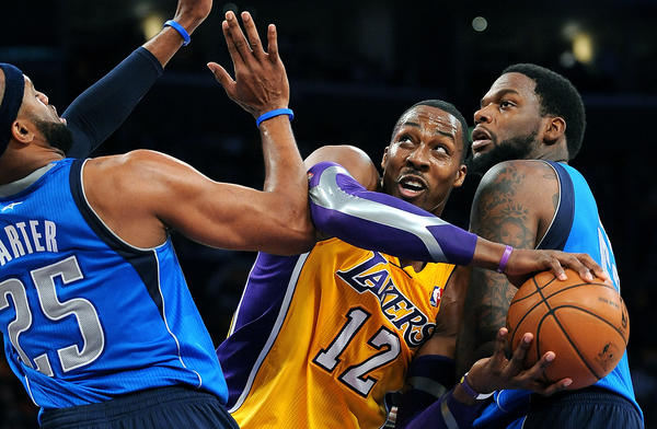 The Lakers' Dwight Howard tries to get around Maverick defenders Vince Carter and Eddy Curry.
