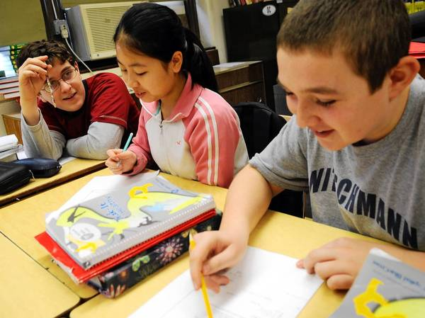 Stephen John Kounoupis (left), Angela Li and Logan Timar work on a math problem together in Mike O'Connell's seventh-grade Algebra I class at Nitschmann Middle School. Algebra I used to be a high school course but more and more middle schoolers are being asked to take it as part of nationwide school standards.