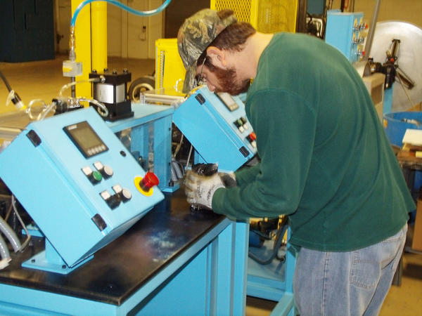 Aaron Moore, an information technology and production employee of ACAT Global, looks over the product formed by a cut and stack machine at the companys recently opened Charlevoix manufacturing plant. The machine aids in forming the metal substrates which the company produces for use in catalytic converters.