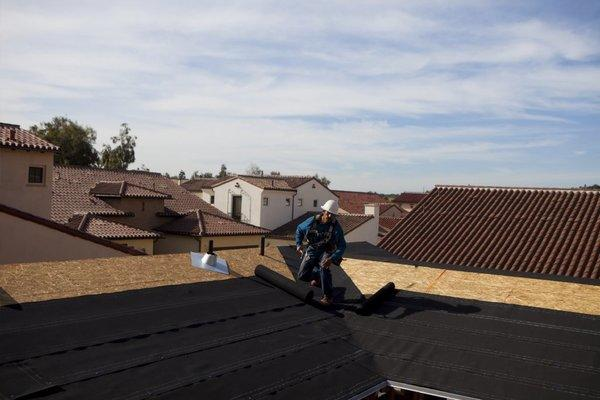 A worker holds a hammer as he unrolls roofing material on a house under construction in Rancho Santa Fe.
