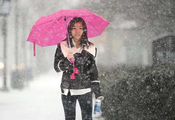 Penn State University student Siyi Sun walks along campus in State College, Pa., as heavy snow falls.