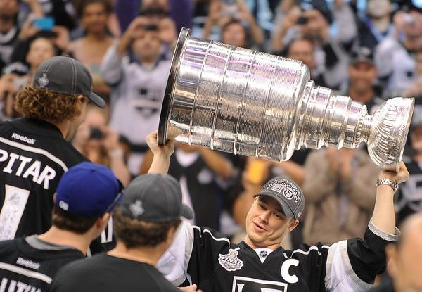 "Kings captain Dustin Brown carries the Stanley Cup during the championship rally at the Staples Center, where legions of fans packed every seat, and players, team officials and dignitaries addressed the crowd. Luc Robitaille, Kings president of business operations, told the team, ""You have changed this city."""