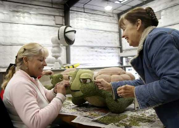 Volunteers Tracy Armijo and Connie Weir apply split peas to one of three turtles that will ride on this years Rose Float 'Deep Sea Adventure'.
