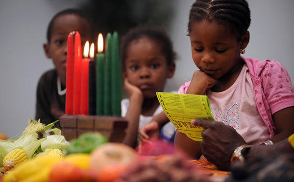 Ariel Henry, 5, of Dania Beach reads one of the seven values Kwanzaa as Shelah Polk, 5, of Coral Springs looks on during the Kwanzaa cermony at the Dr. Martin Luther King Community Center in Hollywood. Kwanzaa is an African American and Pan-African holiday which celebrates family, community and culture over 7 days.