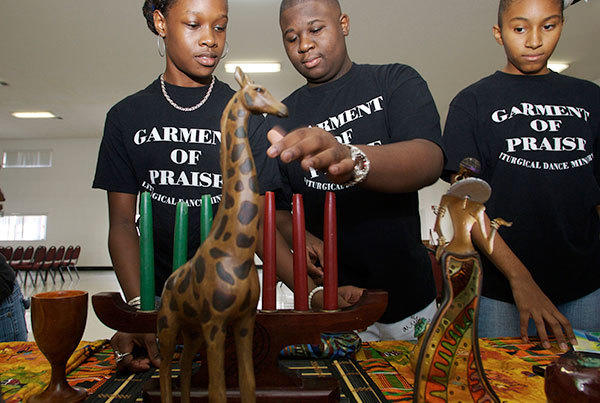 The Garment of Praise dance group is  leading the Palm Beach Kwanzaa celebration this year at there Church St. Johns Missionary Baptist Church in Boynton Beach. (pictured) L_R A'Keyah Williams, De'Vonte Watson and Briana Sullivan un-pack Kwanzaa decorations.