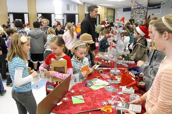 A packed multi-purpose room of parents and fifth-graders shop at the annual fifth grade Top of the World Christmas holiday boutique sale.