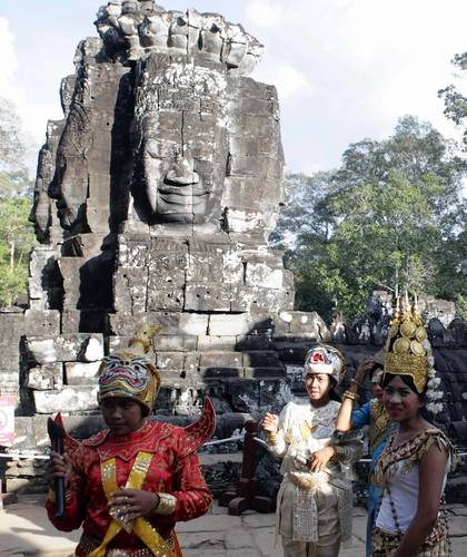 Cambodians wearing native costumes wait for tourists to have their pictures taken for a fee inside Bayon temple in Siem Reap December 22, 2012.