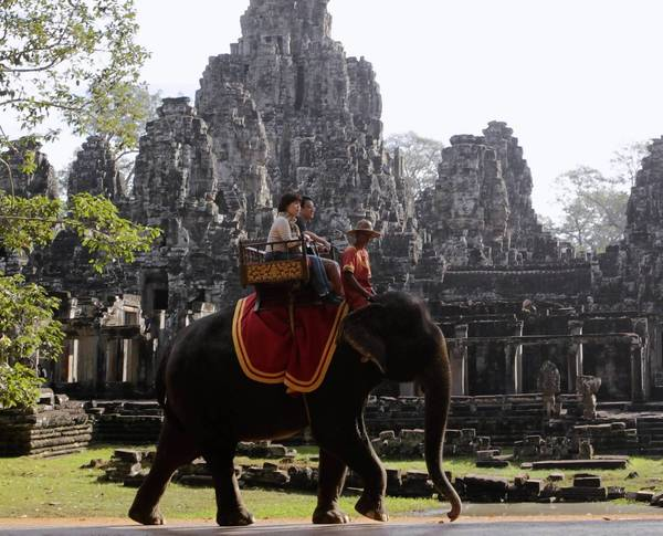 Tourists ride an elephant past the ruins of Cambodia's Bayon temple in Siem Reap December 22, 2012.