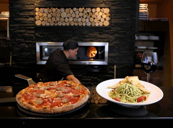 Pasta del giardino, right, and the Tartini pizza at Tartini Pizzeria & Spaghetteria.