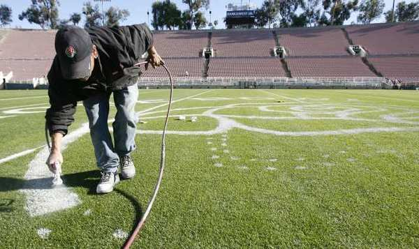 Martin Rodriguez, with the Rose Bowl Operating Company for 13 years, paints the rose artwork at the 50-yard-line at the Rose Bowl in Pasadena on Thursday, December 20, 2012..
