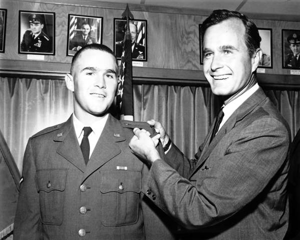 George H.W. Bush, then a congressman from Houston, Texas, pins bars onto the uniform of son George W. Bush signifying the younger Bush's commissioning in the Air National Guard as a 2nd lieutenant, in 1968.