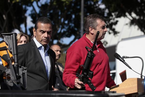 Mayor Antonio Villaraigosa looks at a trash can full of assault weapons while LAPD Chief Charlie Beck holds an assault weapon, one of several turned in, during a news conference.