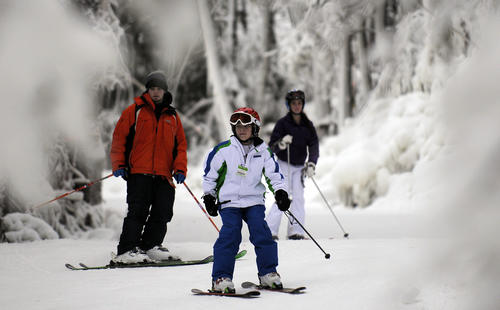 Instructor Alex Hayes (L) guides Trey Albani, 11 (C) and his sister Bella, 14, down Temptor Wednesday afternoon during opening day at Ski Sundown in New Hartford. The ski area has been making snow to get ready for school vacation week and boasts seven trails and all lifts open, snow is in the forecast for the overnight then turning to rain in most of the state.