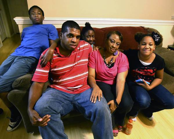 Anthony Slade and Monica Robinson with their children in their south Orlando home. They have benefited from the help of Catholic charities, an organization that is helped by the Family Fund.