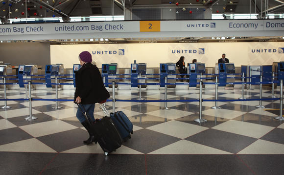 A passenger walks throught the United Airlines terminal.