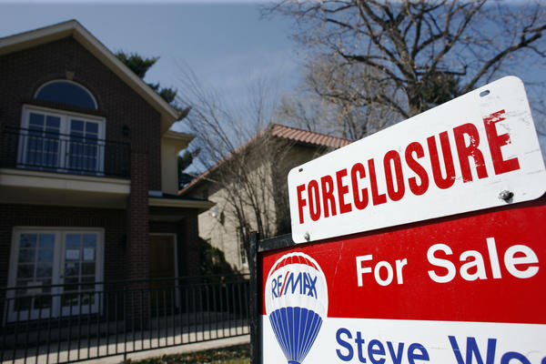 A foreclosure sign sits atop a for sale sign in front of a single-family in Denver, Colo. on April 4, 2010. To stop this harmful lending, the FHA should aim to cut its failure rate roughly in half, setting a maximum foreclosure rate of 10% on the loans it insures with an average foreclosure rate of 5%.