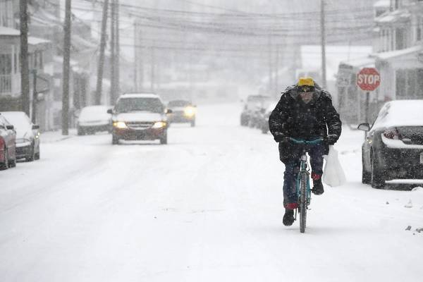 James Hill of Shamokin, Pa., rides his bike in Coal Township, Pa. The storm could dump 12 to 18 inches of snow from the lower Great Lakes to northern New England, the National Weather Service said.