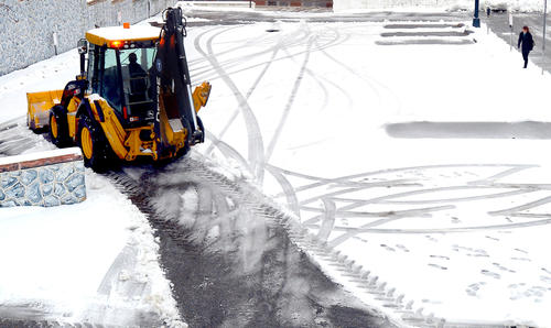 A snowplow operator clears the Rochester lot at the corner of West Washington and South Prospect streets in Hagerstown on Wednesday.