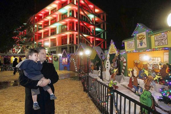 Mark Cordell and his son Jackson, 2, look at the Snoopy House display during the grand opening event at Costa Mesa City Hall Dec. 15.