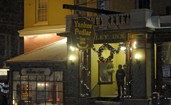 A guest at the Yankee Pedlar Inn in Torrington steps outside for a smoke as a snow storm hit the state Wednesday evening with forecast of 6-9 inches of snow in the Litchfield hills before changing over to rain on Thursday.