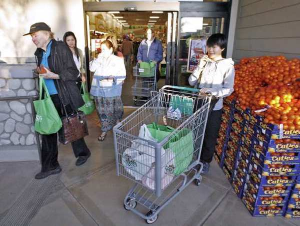 Customers come out of the new Sprouts market in La Canada Flintridge early on Wednesday morning, March 21, 2012. A large line of customers waited outside the store for up to one and a half hours to be the first ones inside.