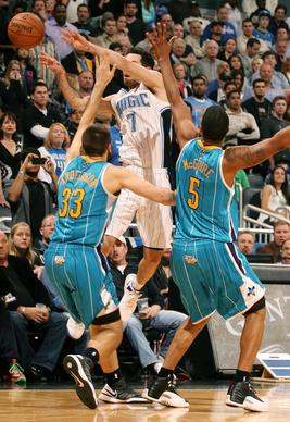 With seconds remaining in the game, the Orlando Magic's J.J. Redick (7) is stopped by the New Orleans Hornets' Ryan Anderson (33) and Dominic McGuire (5) at the Amway Center in Orlando, Florida, on Wednesday, December 26, 2012. New Orleans won, 97-94.