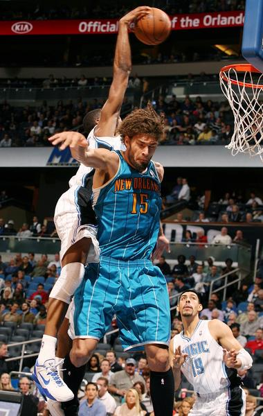 The Orlando Magic's Maurice Harkless, left, drives through the New Orleans Hornets' Robin Lopez (15) as Harkless scores at the Amway Center in Orlando, Florida, on Wednesday, December 26, 2012.
