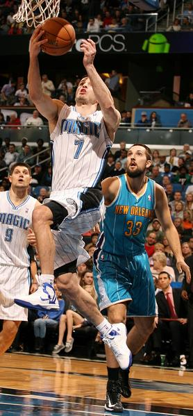 Orlando guard J.J. Redick (7) scores in front of New Orleans forward Ryan Anderson (33) during the New Orleans Hornets at Orlando Magic NBA game at the Amway Center on Wednesday, December 26, 2012.