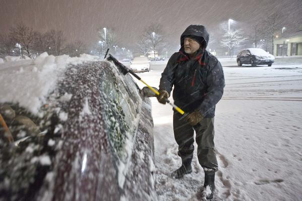Attorney Thomas Mullaney III, a Glastonbury resident removes snow from his car outside Barnes & Noble during the snow storm which hit New England Wednesday evening.