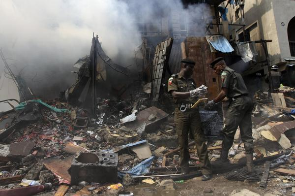 Policemen pick up samples from the rubble after fireworks stored in a building exploded in a densely populated area in the Isale Eko district of Nigeria's commercial capital of Lagos December 26, 2012.