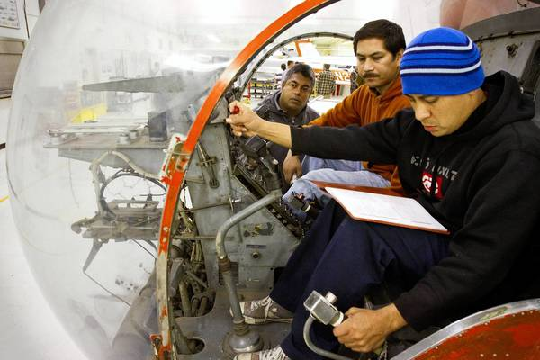 Students Ronald Quijada, Mayko Alonso and Chandana Koralalage, front to back, go through the starting and shutting down procedures on a TH-13T helicopter.