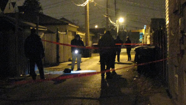 Detectives investigate the scene of a shooting that left a 32-year-old man dead late Wednesday night.