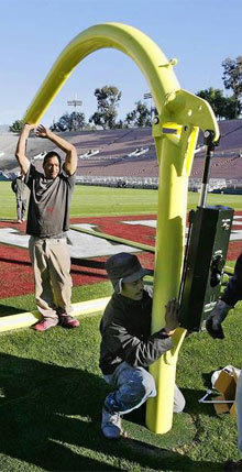 A goal post is put into place at the Rose Bowl in Pasadena in preparation for the game between Wisconsin and Stanford. Everything that goes into preparing for the matchup takes place on a detailed schedule behind the scenes.