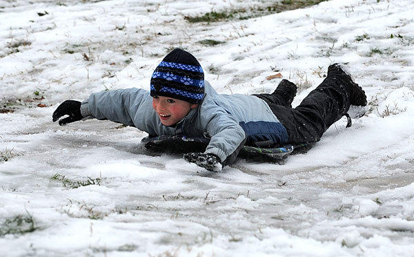 Josh Forrest, almost 9, sleds down a hill at Patterson Park during Wednesday's unexpected snow.