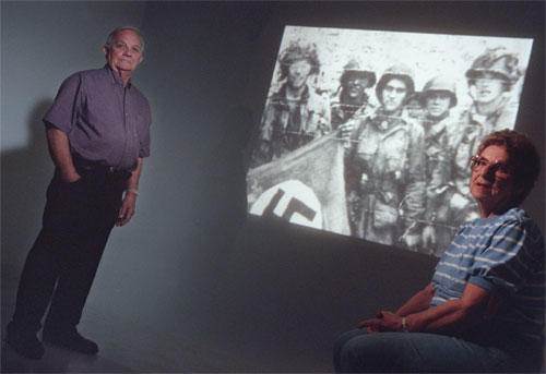 Dick Acker of Breinigsville and his sister, Marion Wagner, appear beside a projection of a newsreel still frame that shows their brother, David (far right), with a group of GIs after the Normandy invasion.