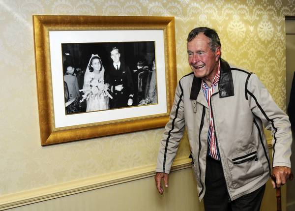 Former President George H.W. Bush walks past a portrait of himself and wife Barbara aboard the aircraft carrier that bears his name, USS George H.W. Bush (CVN 77) in the Atlantic Ocean in 2010. Bush and former first lady Barbara Bush spent their time onboard watching flight operations, touring the ship and visiting with the crew. The George H.W. Bush was conducting training in the Atlantic Ocean.