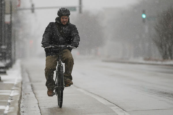 A bicyclist fights the snow heading north on Halsted Street, north of Roosevelt Avenue in Chicago.