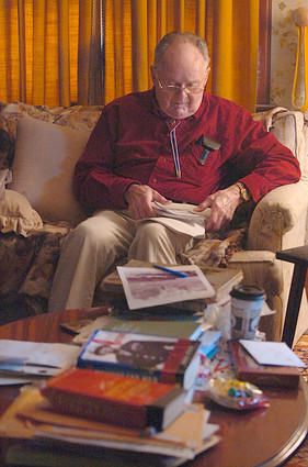 Jack Davis is an 83-year-old decorated Army veteran of World War II. During the Battle of the Bulge, he crawled through the snow on Christmas Eve 1944 to give morphine to a badly wounded German soldier who lay screaming in the night. Davis, a student of World War II, looks over his notes. Some of his many books about the war are on the coffee table in the foreground.