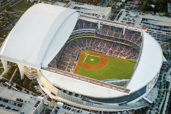 The local baseball team debuts its pricey stadium in Little Havana to a national TV audience, which is treated to scenes that add a new chapter to the South Florida legend: a massive piece of folk-art zaniness by renowned sculptor-painter Red Grooms in center and topless women, lightly glazed in neon-colored paint, shimmying by the pool at the Clevelander bar in left.