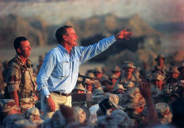 President George H. W. Bush tosses presidential tie clips to U.S. Marines at a desert encampment in eastern Saudi Arabia on May 23, 1990.
