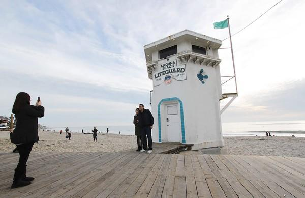 Tourists take pictures in front of an old lifeguard tower on Main Beach on Christmas day.