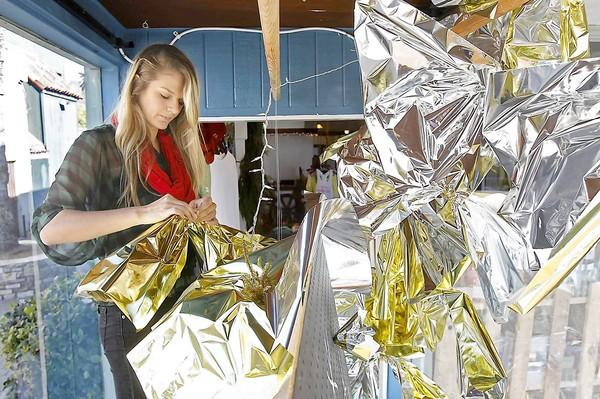 Sydney Hensler wraps giant bow ties for the display window at Toes on the Nose surf shop, a New Year's themed celebration window. Hensler is the creative designer for the popular window displays that catch the eye of passersby in downtown Laguna.